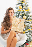 Happy young woman with shopping bag near christmas tree Stock Photo