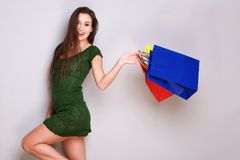 Happy young woman with shopping bags against gray background. Portrait of happy young woman with shopping bags against gray background Royalty Free Stock Photos