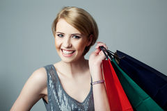 Happy young woman with shopping bags. Against gray wall Stock Image