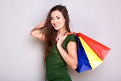 Happy young woman with shopping bags against gray wall. Portrait of happy young woman with shopping bags against gray wall Royalty Free Stock Photography