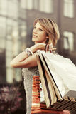 Happy young woman with shopping bags against mall window. Happy young woman with shopping bags walking against mall window Royalty Free Stock Photo