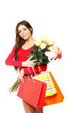 Happy young woman with shopping bags and a bouquet of roses on a. Happy young woman with shopping bags and a bouquet of roses on white background Royalty Free Stock Photos