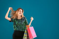 Happy young woman with shopping bags color background Royalty Free Stock Image