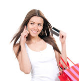 Happy young woman with shopping bags and credit card. In hand talking on phone isolated on a white background Royalty Free Stock Photography