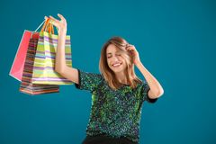 Happy young woman with shopping bags. On color background Stock Image
