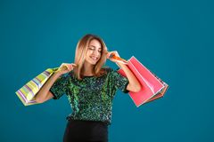 Happy young woman with shopping bags. On color background Stock Photos