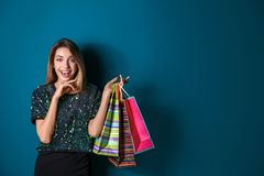 Happy young woman with shopping bags. On color background Royalty Free Stock Photos