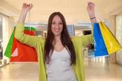 Happy young woman with shopping bags having fun while shopping i. N a mall Royalty Free Stock Image