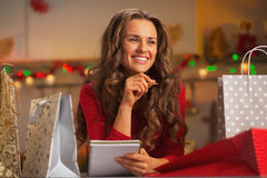 Happy young woman with shopping bags in kitchen. Happy young woman with shopping bags in christmas decorated kitchen checking list of gifts Royalty Free Stock Photo