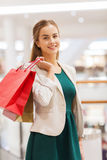 Happy young woman with shopping bags in mall Stock Photos