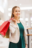Happy young woman with shopping bags in mall. Sale, consumerism and people concept - happy young woman with shopping bags in mall Royalty Free Stock Images