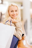 Happy young woman with shopping bags in mall Royalty Free Stock Photography