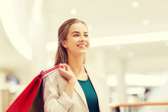 Happy young woman with shopping bags in mall Royalty Free Stock Images