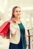 Happy young woman with shopping bags in mall. Sale, consumerism and people concept - happy young woman with shopping bags in mall Stock Photos