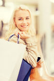 Happy young woman with shopping bags in mall. Sale, consumerism and people concept - happy young woman with shopping bags in mall Royalty Free Stock Photography