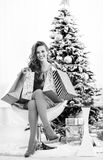 Happy young woman with shopping bags nea. Full length portrait of happy young woman with shopping bags near christmas tree Stock Photography