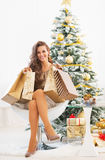 Happy young woman with shopping bags nearchristmas tree. Full length portrait of happy young woman with shopping bags near christmas tree Stock Images