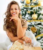 Happy young woman with shopping bags sitting near ch. Portrait of happy young woman with shopping bags sitting near christmas tree Stock Photo