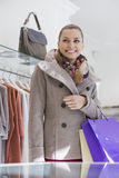 Happy young woman with shopping bags in store Stock Photography