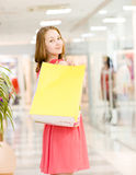 Happy young woman with shopping bags in a supermarket Stock Photography