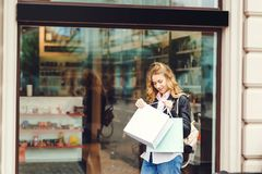 Happy young woman with shopping bags walking on the street. Happy young woman with shopping bags walking on street Royalty Free Stock Image