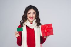 Happy young woman shopping with credit card and holding gift box. On christmas isolated Stock Photos