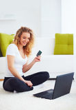 Happy young woman shopping online with laptop at home Stock Images