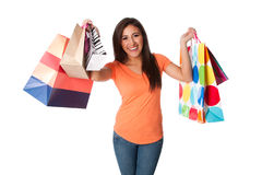 Happy young woman on shopping spree. Beautiful Happy smiling young woman on shopping spree carrying colorful bags with merchandise celebrating, isolated royalty free stock photo