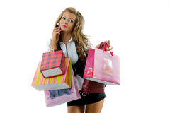 Happy young woman on a shopping spree. Close-up of happy young woman on a shopping spree. Talking by phone. Isolated on white background stock images