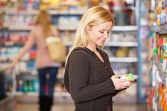 Happy young woman shopping in the supermarket. With people in the background Royalty Free Stock Photography