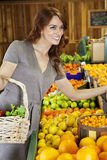 Happy young woman shopping in supermarket for fruits Stock Image