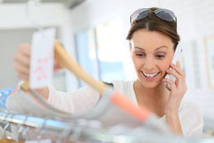 Happy young woman shopping and talking on the phone Royalty Free Stock Image