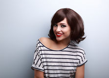 Happy young woman with short hair style toothy smiling. On blue background with empty copy space Stock Image