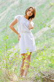 Happy young woman in short white summer dress on green grass Royalty Free Stock Photography