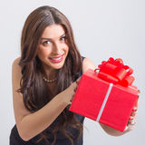 Happy young woman showing big red gift box Stock Photos