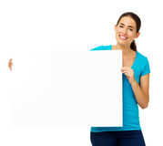 Happy Young Woman Showing Blank Billboard. Portrait of happy young woman showing blank billboard over white background. Horizontal shot Royalty Free Stock Photography