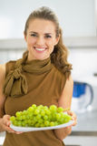Happy young woman showing branch of grapes Stock Photos