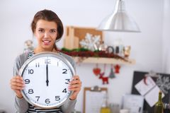 Happy young woman showing clock in christmas Royalty Free Stock Images