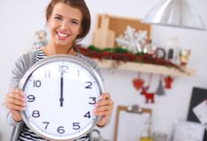 Happy young woman showing clock in christmas Royalty Free Stock Image