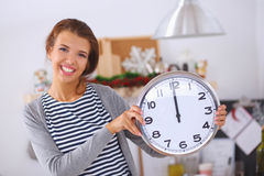 Happy young woman showing clock in christmas Stock Image