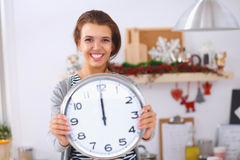 Happy young woman showing clock in christmas Royalty Free Stock Photo