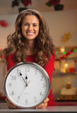 Happy young woman showing clock in christmas decorated kitchen Royalty Free Stock Photo