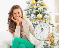 Happy young woman showing clock in front of christmas tree Stock Image