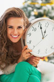 Happy young woman showing clock in front of christmas tree Stock Photos