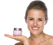 Happy young woman showing cream bottle Royalty Free Stock Photo
