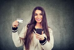 Happy young woman showing credit card while holding mobile phone. Portrait of a happy young woman showing credit card while holding mobile phone on gray stock photos