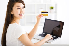 Happy young woman showing credit card and laptop Royalty Free Stock Image