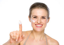 Happy young woman showing creme on finger Stock Image