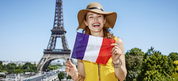 Happy young woman showing French flag in Paris, France Royalty Free Stock Photos
