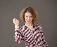 Happy young woman showing a gesture of effort Stock Photography